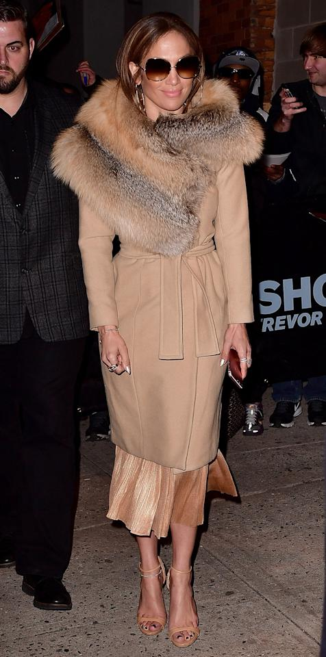 """<p>Lopez left <em>The Daily Show with Trevor Noah</em> while outfitted in head-to-toe beige; the look came together with a lavish fur around her neck, a chic wool coat, a glimmering calf-length dress, and nude sandals (shop a similar pair <a rel=""""nofollow"""" href=""""http://click.linksynergy.com/fs-bin/click?id=93xLBvPhAeE&subid=0&offerid=390098.1&type=10&tmpid=8157&RD_PARM1=http%253A%252F%252Fshop.nordstrom.com%252Fs%252Fstuart-weitzman-nudistsong-ankle-strap-sandal-women%252F3915100%253Forigin%253Dkeywordsearch-personalizedsort%2526fashioncolor%253DNAKED%252520SUEDE&u1=ISJLoSSSandalsIJMarch"""">here</a>).</p>"""