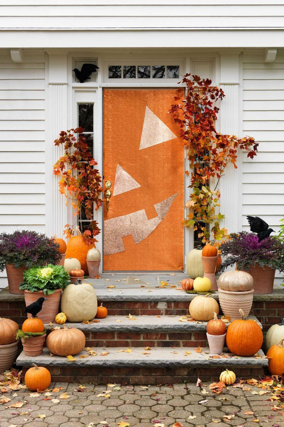 """<p>1. Trim orange wrapping paper to the height of the door; secure with masking tape.</p><p>2. Overlap another sheet to cover the rest of the door; tape down.</p><p>3. Lay gold glitter paper facedown and use a ruler to draw an eye (a triangle with 12"""" sides), nose (a triangle with 10"""" sides) and lopsided smile.</p><p>4. Cut out, arrange and tape to the door as shown.</p><p>5. Cut a small hole in the top of each large pumpkin with a craft knife.</p><p>6. Insert the leaf branches; push down until secure.</p><p>7. To keep the branches upright, tap a picture nail into either side of the door frame; secure each branch with fishing line.</p><p>8. Spray-glue small pumpkins; dust with glitter; let dry.</p><p>9. Arrange cabbages and pumpkins in planters on the steps.</p><p>10. Add faux crows, if desired; secure with fishing line as needed.</p>"""
