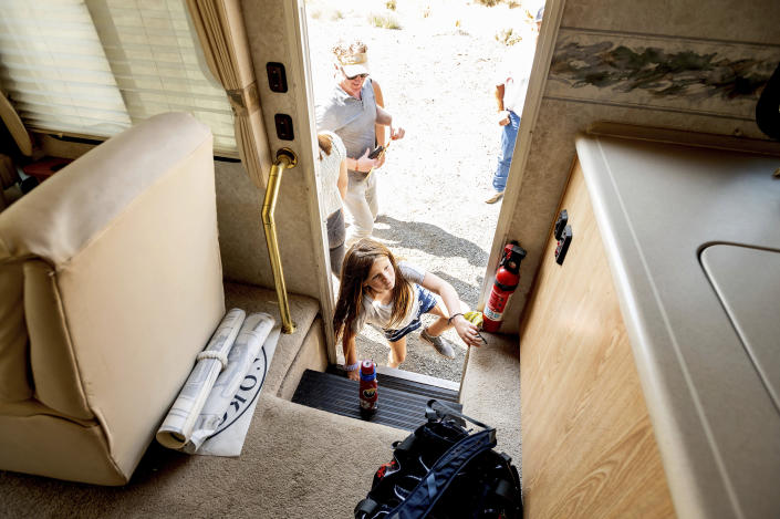Luna Faircloth boards a donated RV while delivering it to a Dixie Fire victim on Sunday, Sept. 5, 2021, in Sierra County, Calif. Behind her is dad Woody Faircloth who runs the non-profit EmergencyRV.org. (AP Photo/Noah Berger)