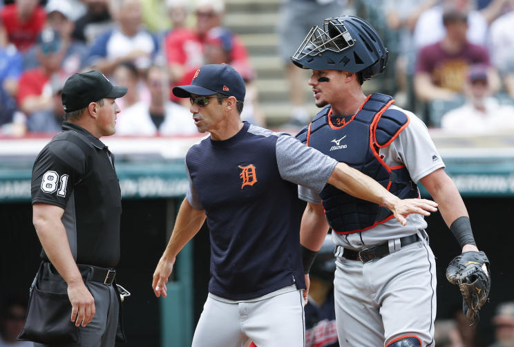 Home plate umpire Quinn Wolcott argues with Tigers manager Brad Ausmus and catcher James McCann moments before being hit by a questionable pitch. (AP)