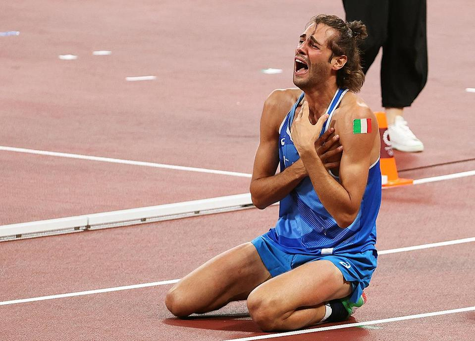<p>Gianmarco Tamberi of Italy drops to his knees after earning gold in the Men's High Jump Final at Olympic Stadium on August 1.</p>
