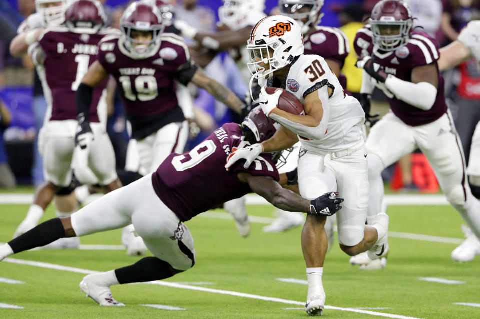 Oklahoma State running back Chuba Hubbard (30) is caught by Texas A&M defensive back Leon O'Neal Jr. (9) during the first half of the Texas Bowl NCAA college football game Friday, Dec. 27, 2019, in Houston. (AP Photo/Michael Wyke)