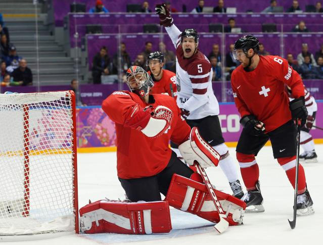 Latvia forward Janis Sprukts (5) reacts as the puck gets past Switzerland goaltender Jonas Hiller for a goal in the first period of a men's ice hockey game at the 2014 Winter Olympics, Tuesday, Feb. 18, 2014, in Sochi, Russia. (AP Photo/Mark Humphrey)
