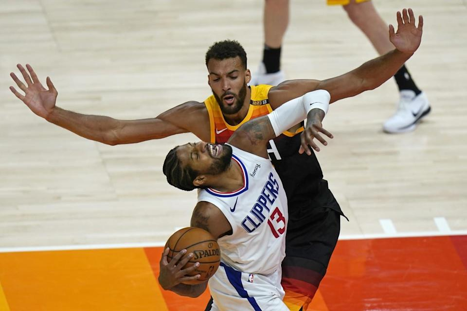 Clippers forward Paul George is knocked off balance on a drive against Jazz center Rudy Gobert.