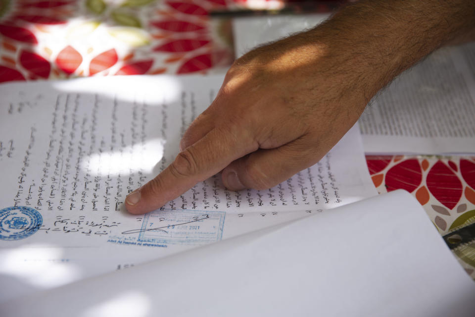 Adel Budeiri points to a document in a court case for several Palestinian families, including his own, who are at risk of forcible eviction from their homes in the Sheikh Jarrah neighborhood of east Jerusalem, Sunday, May 9, 2021. Dozens of Palestinian families in east Jerusalem are at risk of losing their homes to Jewish settler groups following a decades-long legal battle. (AP Photo/Maya Alleruzzo)
