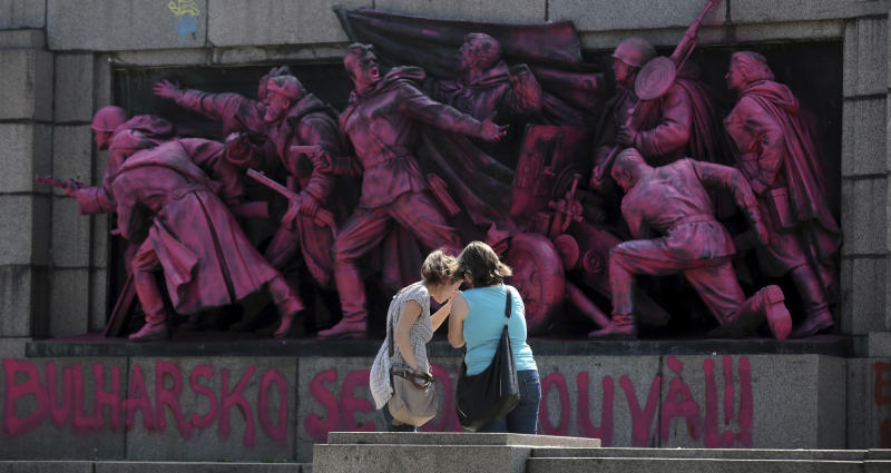 "People stand in front of a Soviet Army monument colored pink by unknown people to mark the anniversary of the Prague Spring with an inscription in Bulgarian and Czech below reading ""Bulgaria apologizes."" in Sofia, Wednesday, Aug. 21, 2013. Bulgaria, which marched in lock step with the Soviet Union for decades, was the first country to insist on the invasion and the last one to formally apologize for its participation – with a declaration of Parliament in 1990, and in 1997, during a presidential visit to Prague. (AP Photo/Valentina Petrova)"