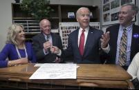 Democratic presidential candidate former Vice President Joe Biden hands the pen to New Hampshire Secretary of State Bill Gardner, second from left, after filing to have his name listed on the New Hampshire primary ballot, Friday, Nov. 8, 2019, in Concord, N.H. At left is his wife Jill Biden. (AP Photo/Charles Krupa)