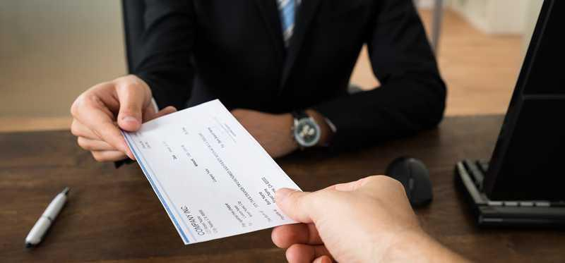 Person in suit handing over a check to another person.