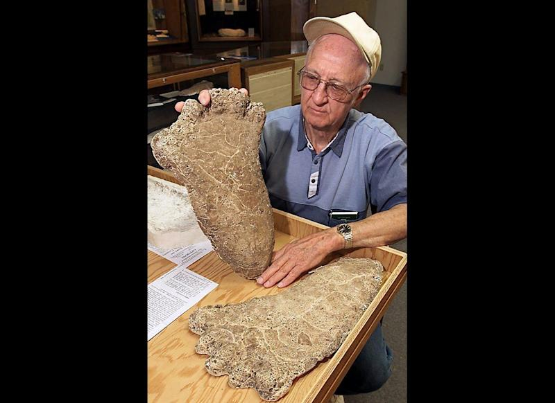 Al Hodgson, a volunteer guide at the Willow Creek-China Flat Museum, holds up a plaster cast of a Bigfoot imprint displayed at the museum's Bigfoot Wing in Willow Creek, Calif., on June 5, 2000. The wing was built to bring tourists interested in the legendary creature to the economically depressed ex-lumber town.