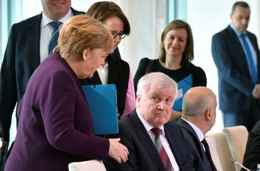 German Chancellor Angela Merkel (L) reaches out to try and shake hands with German Interior Minister Horst Seehofer