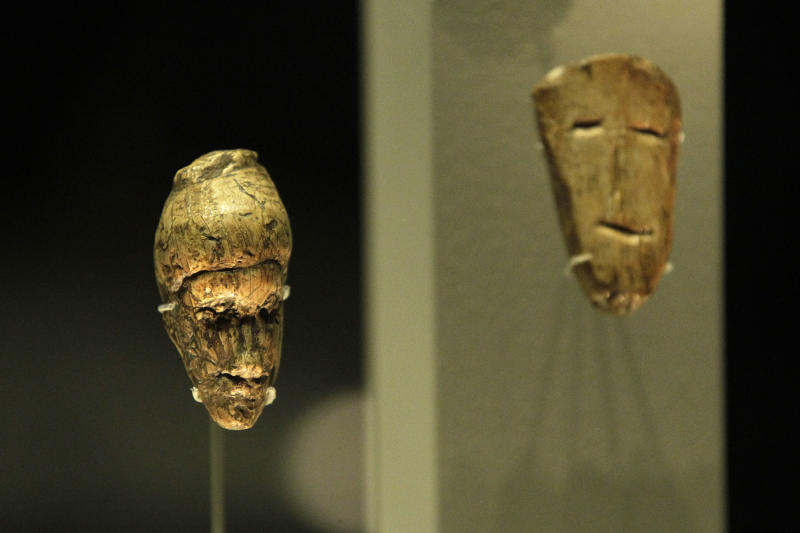 An oldest known portrait of a woman, left, a miniature sculptured from mammoth ivory dates at least 27,000 old, and a sketched human face engraved on a flake of mammoth ivory, both discovered at Dolni Vestonice, Moravia, Czech Republic are seen on display in an exhibition 'Ice Age Art : arrival of the modern mind' at the British Museum in London, Tuesday, Feb. 5, 2013. The sculpture The exhibition present masterpieces create from the last Ice Age between 40,000 and 10,000 years ago, drawn from across Europe, by artists with modern minds and presented alongside modern works to illustrate the fundamental human desire to communicate and make art as a way of understanding ourselves and our place in the world. (AP Photo/Sang Tan)