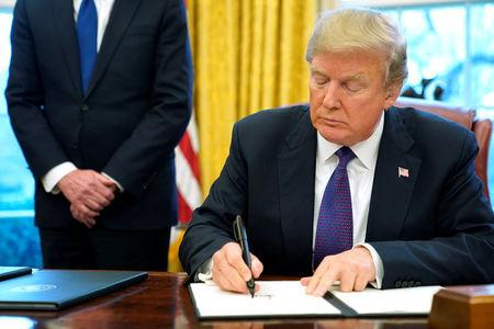 U.S. President Donald Trump signs a directive to impose tariffs on imported washing machines in the Oval Office at the White House in Washington, U.S. January 23, 2018.  REUTERS/Jonathan Ernst