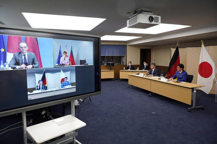 """Japanese Foreign Minister Toshimitsu Motegi, second from right, and Japanese Defense Minister Nobuo Kishi, right, attend a video conference with German Foreign Minister Heiko Maas, top left on screen, and German Defense Minister Annegret Kramp-Karrenbauer, top right on screen, at Foreign Ministry in Tokyo during their """"2 plus 2"""" ministerial meeting Tuesday, April 13, 2021. (Frank Robichon/Pool Photo via AP)"""