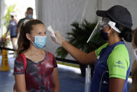 A guest has her temperature checked before entering SeaWorld as it reopens with new safety measures in place because of the coronavirus pandemic, Thursday, June 11, 2020, in Orlando, Fla. The park had been closed since mid-March to stop the spread of the new coronavirus. (AP Photo/John Raoux)