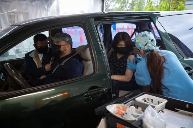 Nurse Melissa Townsend, right, administers the Moderna COVID-19 vaccine to Rowena Cando as her husband Israel Cando sits in the driver's seat of a vehicle at a Fraser Health drive-thru vaccination site, in Coquitlam, B.C., on Wednesday, May 5, 2021.