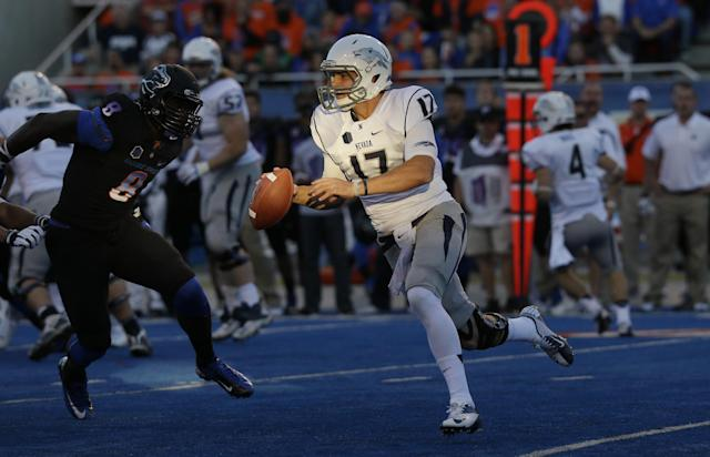 Nevada quarterback Cody Fajardo (17) scrambles through a patch of sunlight on the field as he tries to pass under pressure from Boise State defensive end Demarcus Lawrence, left, in the first half of an NCAA college football game, Saturday, Oct. 19, 2013 in Boise, Idaho. (AP Photo/Ted S. Warren)