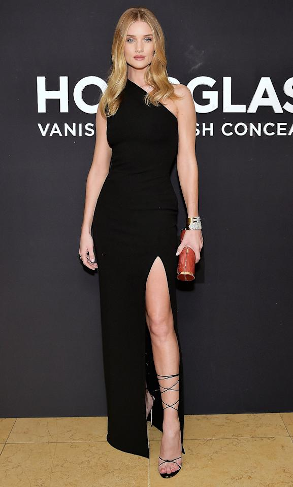 in a black one-shoulder gown featuring a thigh-high slit, teamed with strappy black tie-up stilettos, David Webb jewels and a red barrel clutch with gold trim at the launch of Hourglass x Rosie Huntington-Whiteley in L.A.