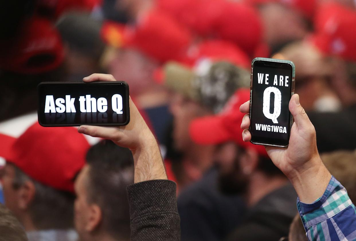 Supporters of President Donald Trump hold up their phones with messages referring to the QAnon conspiracy theory at a campaign rally at Las Vegas Convention Center on February 21, in Las Vegas, Nevada.