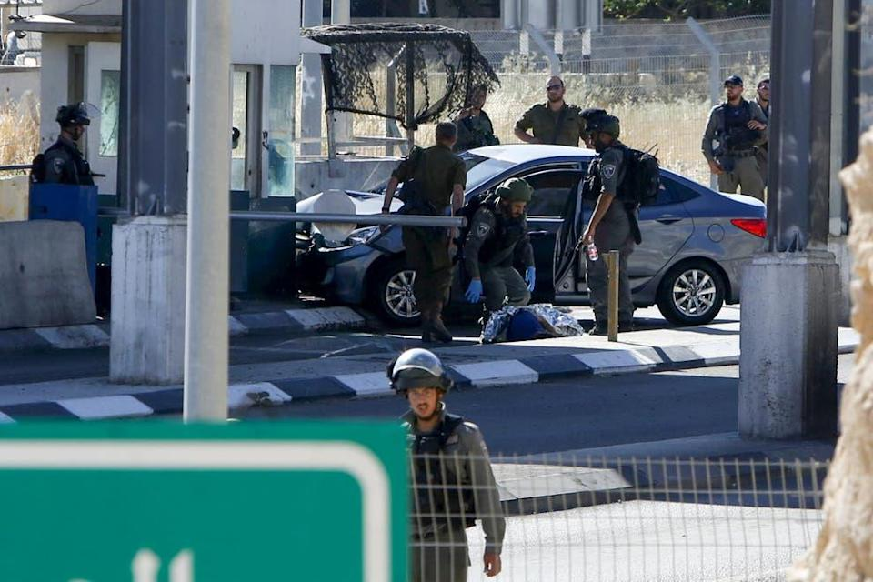 <p>Israeli forces cover the body of Ahmed Erekat</p> (AFP/Getty)
