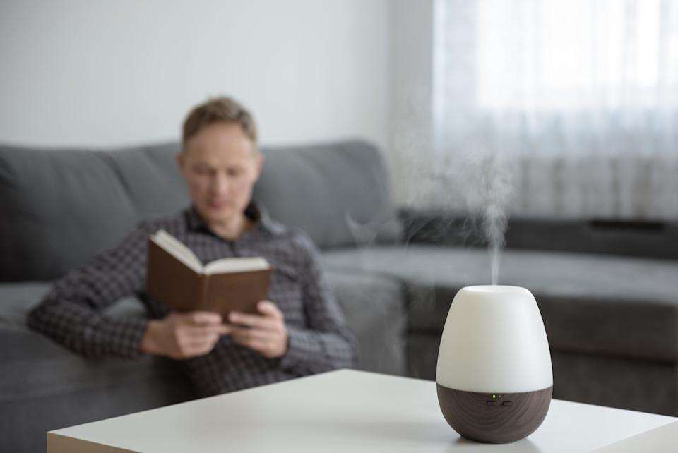 Aromo diffuser on a white table on the background of the interior. In the background, a man is reading a book.