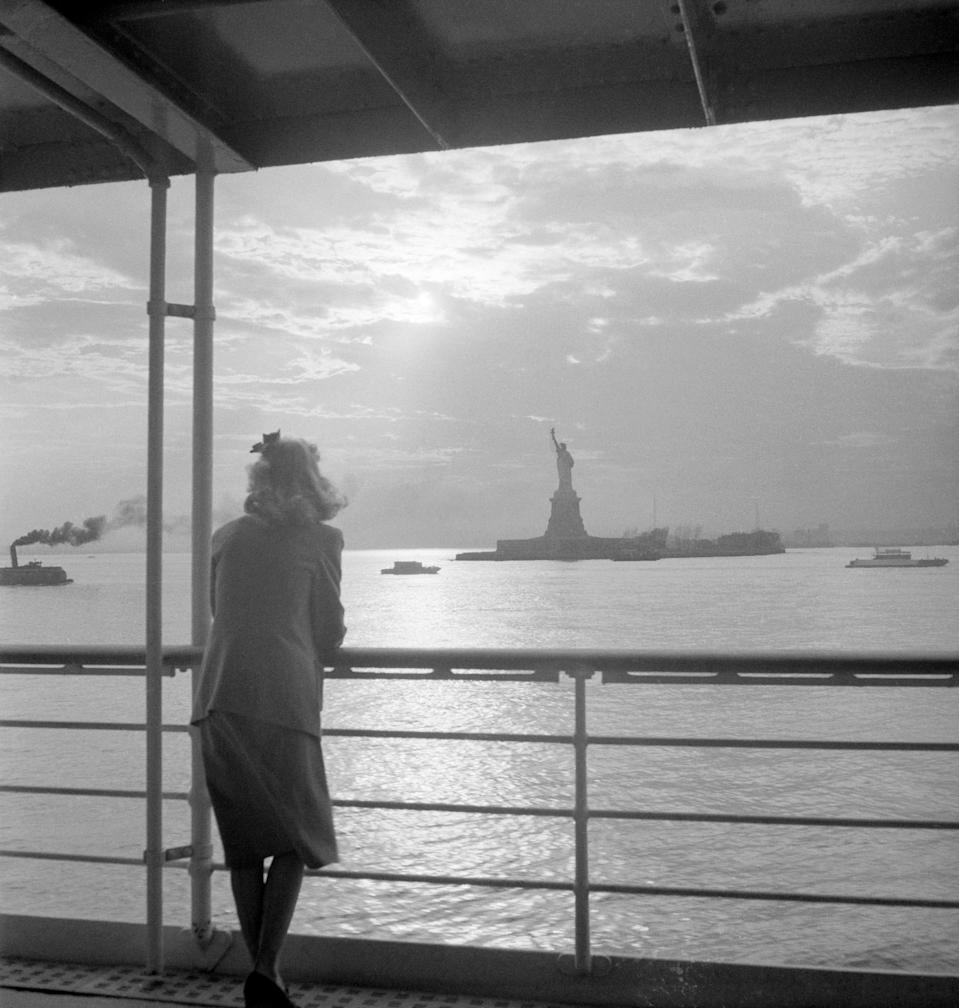 "A woman gazes out at the <a href=""https://www.cntraveler.com/activities/new-york/statue-of-liberty?mbid=synd_yahoo_rss"" rel=""nofollow noopener"" target=""_blank"" data-ylk=""slk:Statue of Liberty"" class=""link rapid-noclick-resp"">Statue of Liberty</a> from the deck of a ferry. The iconic statue, built in France, was given by the country as a gift to the United States in honor of the U.S. centennial of independence. It was shipped overseas in parts, and then reconstructed on what is now known as Liberty Island—less than a mile away from <a href=""https://www.cntraveler.com/activities/ellis-island?mbid=synd_yahoo_rss"" rel=""nofollow noopener"" target=""_blank"" data-ylk=""slk:Ellis Island"" class=""link rapid-noclick-resp"">Ellis Island</a>—and was unveiled in 1886."