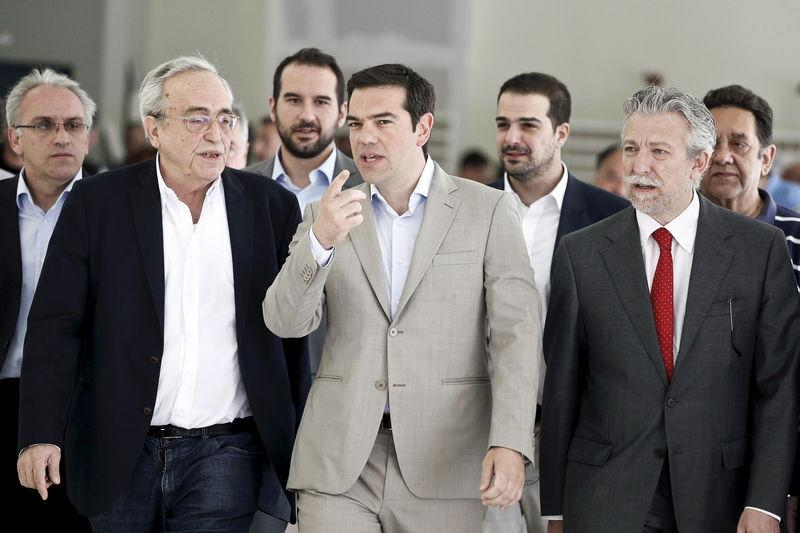 Greek PM Tsipras gestures as he is escorted by Baltas, Kontonis and Sakellaridis during his visit at the ministry in Athens