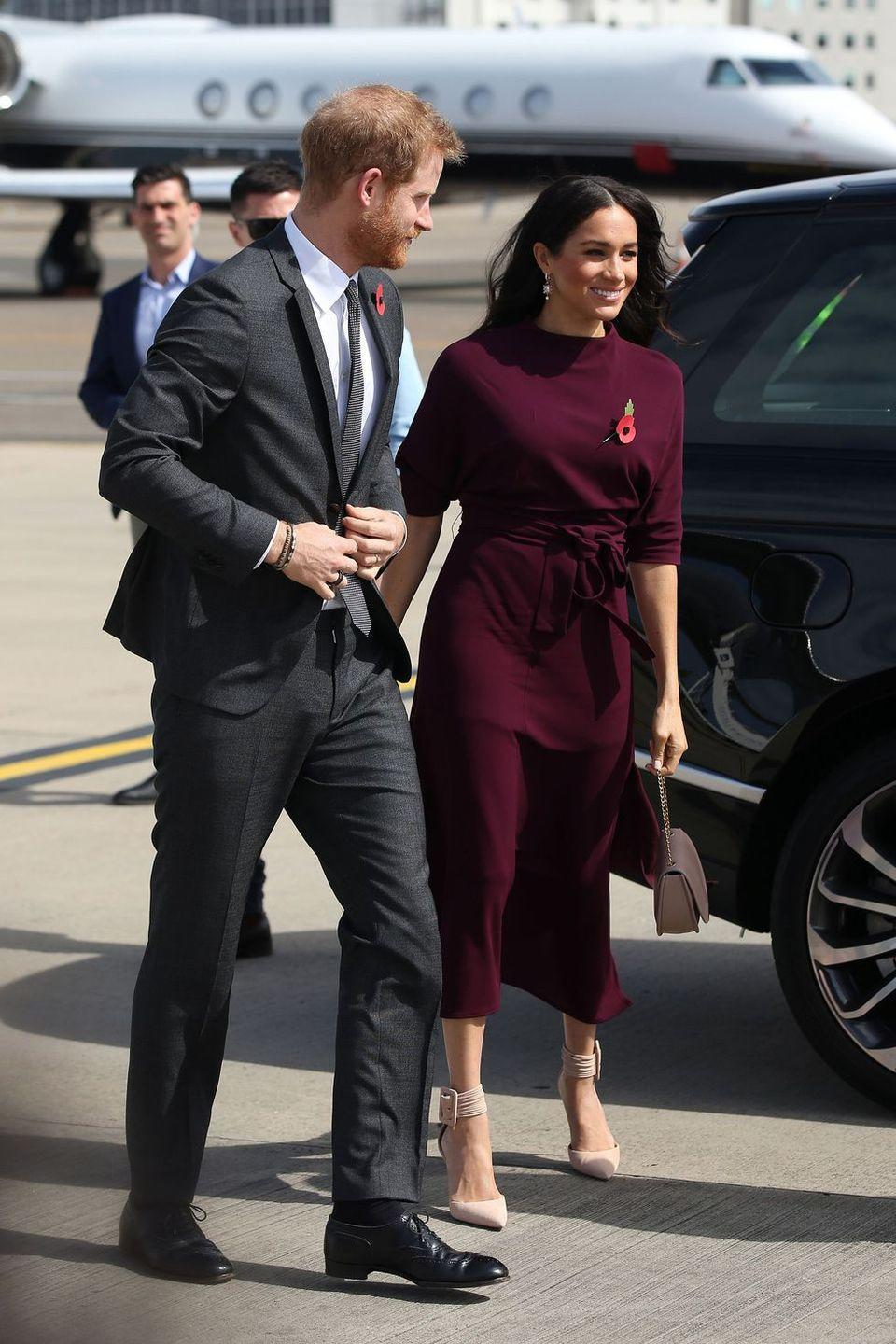 "<p>The couple left for the final country on their royal tour schedule, New Zealand, on Sunday, October 28. The Duchess wore a burgundy Hugo Boss dress for the travel day.</p><p><a class=""link rapid-noclick-resp"" href=""https://go.redirectingat.com?id=74968X1596630&url=https%3A%2F%2Fwww.hugoboss.com%2Fuk%2Fslim-fit-dress-in-soft-jersey-with-detachable-belt%2F4029049659730.html&sref=https%3A%2F%2Fwww.townandcountrymag.com%2Fstyle%2Ffashion-trends%2Fg3272%2Fmeghan-markle-preppy-style%2F"" rel=""nofollow noopener"" target=""_blank"" data-ylk=""slk:SHOP NOW"">SHOP NOW</a><em> Soft Jersey Dress by Hugo Boss, $319</em></p>"