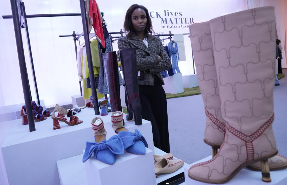 Fashion designer Judith Borsetto, founder of label Judith Saint Jermain, poses in front of her creations, part of the Black Lives Matter Spring Summer 2022 collective fashion event, unveiled during the Milan Fashion Week, in Milan, Italy, Tuesday, Sept. 21, 2021. (AP Photo/Antonio Calanni)