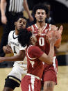 Arkansas forward Justin Smith (0) passes the ball to guard Davonte Davis (4) as Vanderbilt guard Jordan Wright (4) defends during the first half of an NCAA college basketball game Saturday, Jan. 23, 2021, in Nashville, Tenn. (AP Photo/Mark Zaleski)