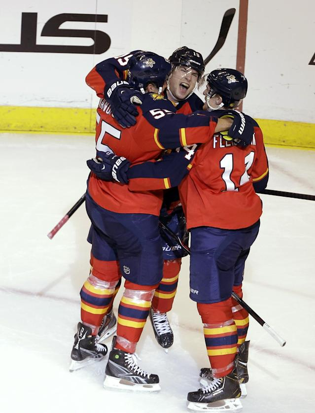 Florida Panthers' Scottie Upshall, center, celebrates with Ed Jovanovski (55) and Tomas Fleischmann (14) after scoring a goal during the second period of an NHL hockey game against the New York Islanders, Tuesday, Jan. 14, 2014, in Sunrise, Fla. (AP Photo/Lynne Sladky)