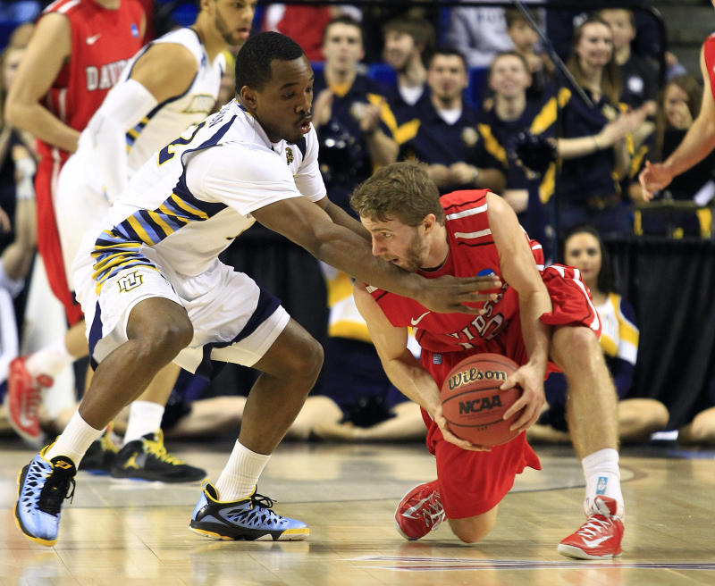 Davidson guard Nik Cochran (12) and Marquette guard Trent Lockett (22) fight for the ball during the first half of a second-round game in the NCAA college basketball tournament, Thursday, March 21, 2013, in Lexington, Ky.  (AP Photo/James Crisp)