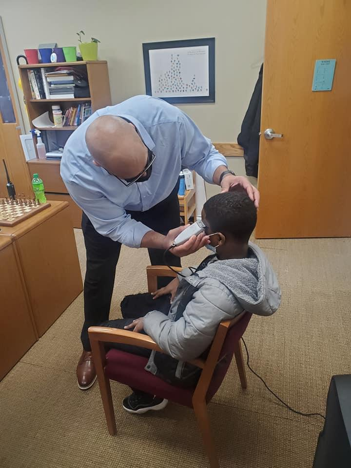 Jason Smith, the principal at Stonybrook Intermediate and Middle School, cuts a student's hair Feb. 18, 2021.