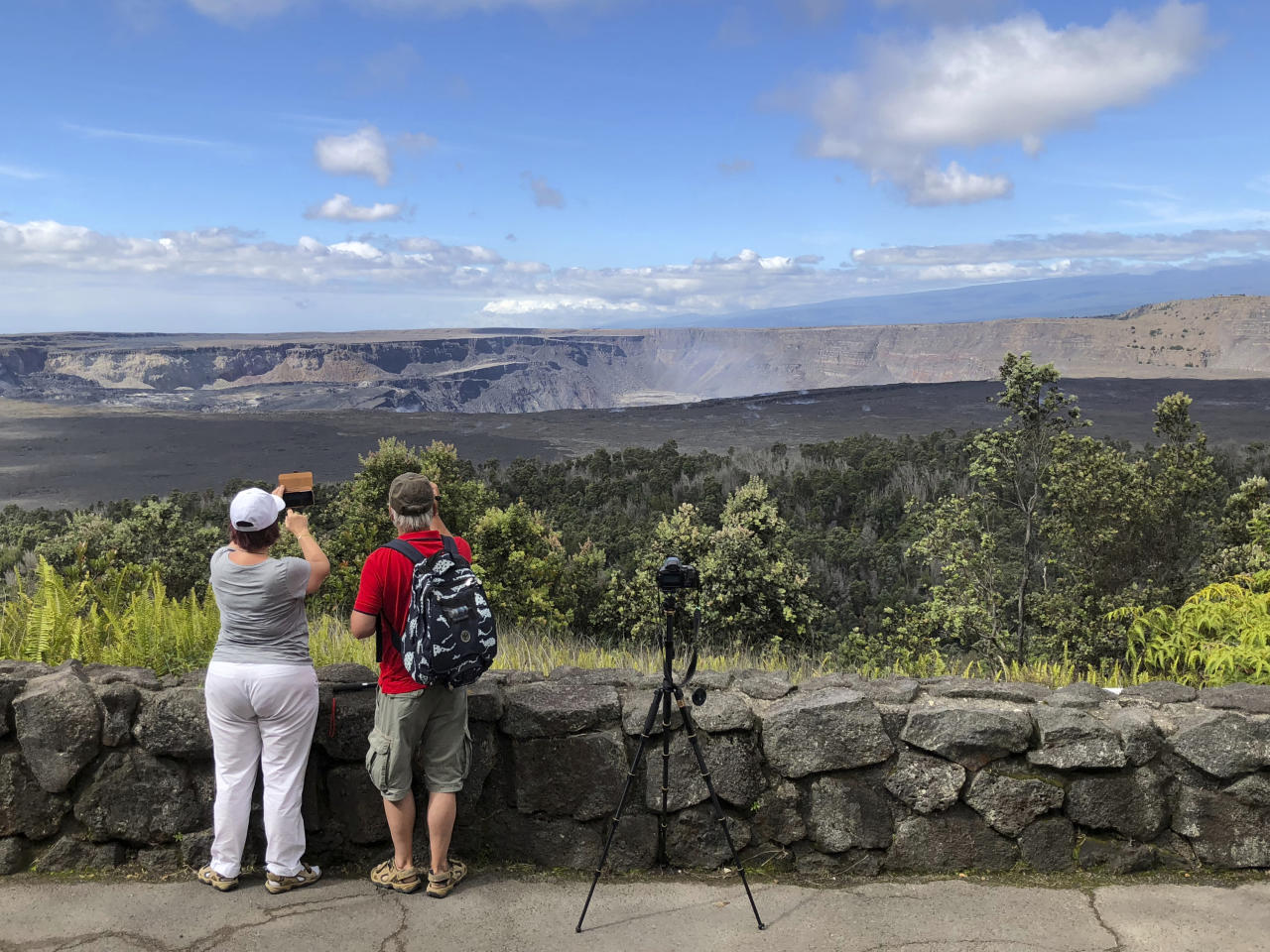 This Saturday, Sept. 22, 2018 photo released by the National Park Service shows tourists on the first day the park was reopened after volcanic activity forced Hawaii Volcanoes National Park to close for more than four months in Hawaii. The eruption destroyed hundreds of homes outside the park while changing the popular summit crater inside the park. (Janice Wei/National Park Service via AP)
