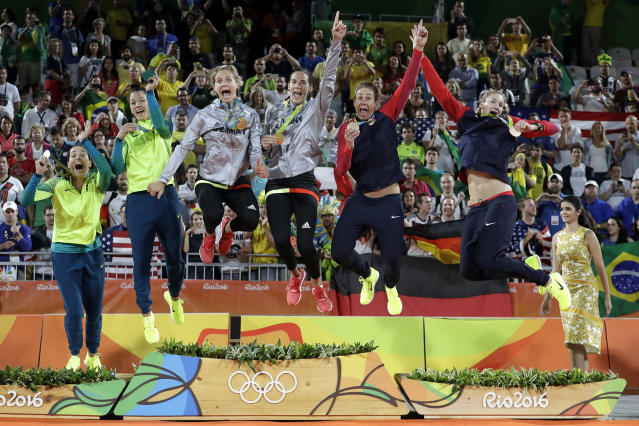 <p>Medalists jump off the podium after the medals ceremony in the women's beach volleyball competion of the 2016 Summer Olympics in Rio de Janeiro, Brazil, Aug. 18, 2016. From left are, Brazil's Agatha Bednarczuk and Barbara Seixas de Freitas with the silver medal, Germany's Laura Ludwig and Kira Walkenhorst with the gold medal, and United States' April Ross and Kerri Walsh Jennings with the bronze medal. (Photo: Marcio Jose Sanchez/AP) </p>