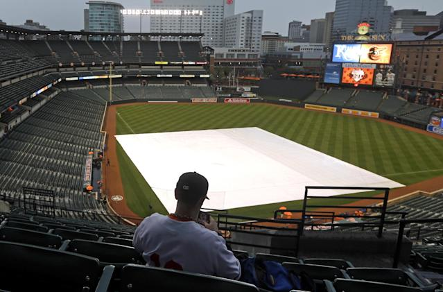 Mark Kittelberger, of Columbia, Md., sits alone in the upper deck as a tarp covers the infield before a scheduled baseball game between the Kansas City Royals and the Baltimore Orioles, Friday, April 25, 2014, in Baltimore. The rain caused officials to delay the start of the game. (AP Photo/Patrick Semansky)