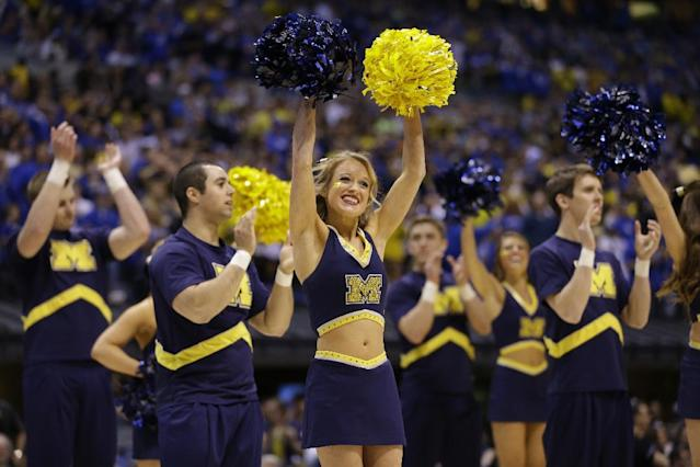 Michigan cheerleaders perform before an NCAA Midwest Regional final college basketball tournament game against Kentucky Sunday, March 30, 2014, in Indianapolis. (AP Photo/Michael Conroy)
