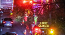 Authorities work to clear a fallen tree that is blocking a lane on I-20 at Langhorn Street in Atlanta on Thursday morning, Oct. 29, 2020. Tropical Storm Zeta sped across the Southeast on Thursday, leaving a trail of damage and more than 2 million homes and businesses in the dark in Atlanta. (John Spink/Atlanta Journal-Constitution via AP)