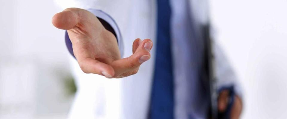 Male medicine doctor offering helping hand in office closeup. Friendly and cheerful gesture. Medical cure and tests advertisement concept. Physician ready to examine and save patient
