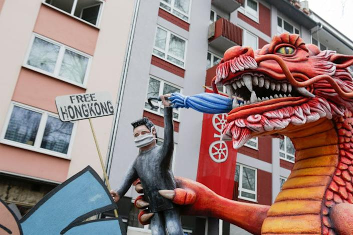 "A protester holding a placard that says ""Free Hong Kong"" in the paw of a large red dragon, representing China, is depicted on a float in the Mainz Rose Monday parade in Germany on February 24, 2020."