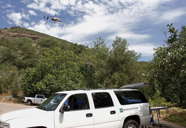 <p>A Department of Public Safety helicopter hovers over as a mortuary vehicle awaits for victims on the parking lot of Water Well Campground in the Tonto National Forest, Ariz, Sunday morning, July 16, 2017, following Saturday's deadly flash-flooding at Cold Springs canyon. (Alexis Bechman/Payson Roundup via AP) </p>
