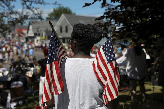 <p>A woman holds U.S. flags during a parade marking Independence Day in Deer Isle, Maine, July 4, 2017. (Photo: Shannon Stapleton/Reuters) </p>