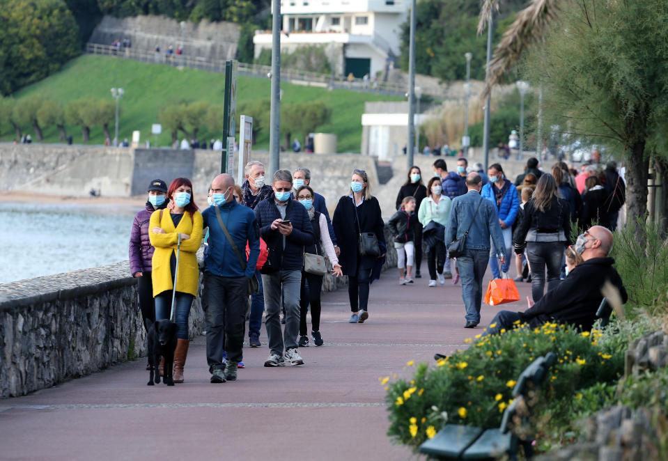 People wearing masks to protect against coronavirus, walk, near the Atlantic Ocean in Saint Jean de Luz, southwestern France, Saturday Oct. 17, 2020. France became the latest European country to toughen anti-coronavirus measures, imposing a curfew in Paris and eight other cities from Saturday. (AP Photo/Bob Edme)