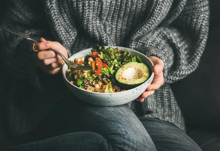 Healthy vegetarian dinner. Woman in grey jeans and sweater eating fresh salad, avocado half, grains, beans, roasted vegetables from Buddha bowl