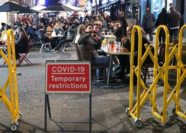 People eating and drinking in Soho, central London, next to a sign warning of Covid-19 restrictions (Yui Mok/PA)