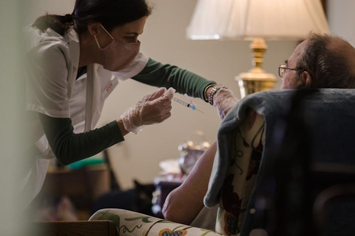 A pharmacist administers a dose of a COVID-19 vaccine