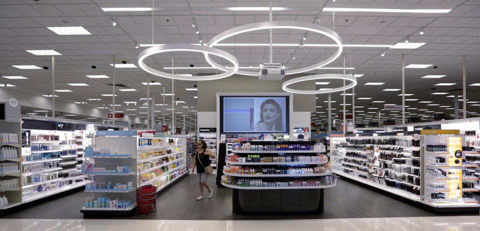 In this May 30, 2018, photo, a shopper walks through the updated cosmetic department at a Target store in San Antonio. Success of specialty chains like Sephora and Ulta has pushed discounters like Walmart and Target as well as drugstores like CVS to revamp their cosmetics areas with more open spaces, brighter lighting and more attractive fixtures. (AP Photo/Eric Gay)