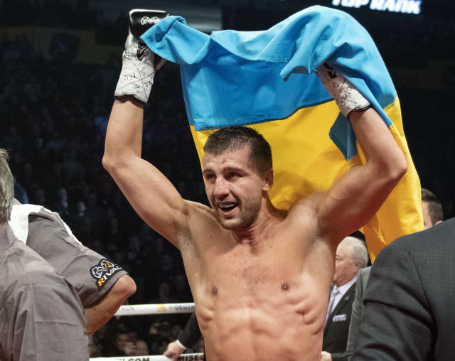 Oleksandr Gvozdyk raises the Ukrainian flag to celebrate his win over Adonis Stevenson, of Canada, and winning the light heavyweight WBC championship boxing fight, Saturday, Dec. 1, 2018, in Quebec City. (Jacques Boissinot/The Canadian Press via AP)