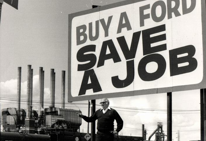 Mike Rinaldi, then-President of UAW Local 600, stands at the sign in front of his headquarters on Dix and points to the Ford Rouge Plant in 1983.