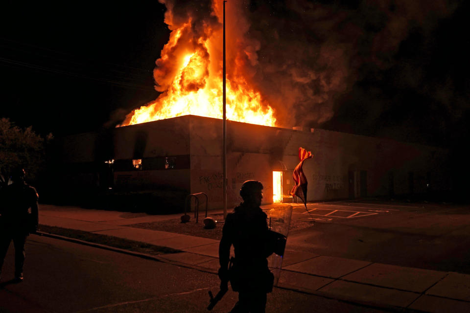 An American flag falls from its pole as police attempt to secure the area after protesters set fire to the department of corrections building, Aug. 24, 2020, in Kenosha, Wis. Protests have erupted following the police shooting of Jacob Blake a day earlier. The image was part of a series of photographs by The Associated Press that won the 2021 Pulitzer Prize for breaking news photography. (AP Photo/David Goldman)
