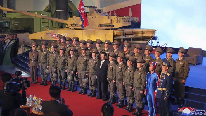 """In this photo provided by the North Korean government, North Korean leader Kim Jong Un, center, poses for a group photo with fighter pilots who made the demonstration flight at the opening of an exhibition of weapons systems in Pyongyang, North Korea, Monday, Oct. 11, 2021. Kim reviewed the rare exhibition and vowed to build an """"invincible"""" military, as he accused the United States of creating regional tensions and lacking action to prove it has no hostile intent toward the North, state media reported Tuesday. Independent journalists were not given access to cover the event depicted in this image distributed by the North Korean government. The content of this image is as provided and cannot be independently verified. Korean language watermark on image as provided by source reads:"""